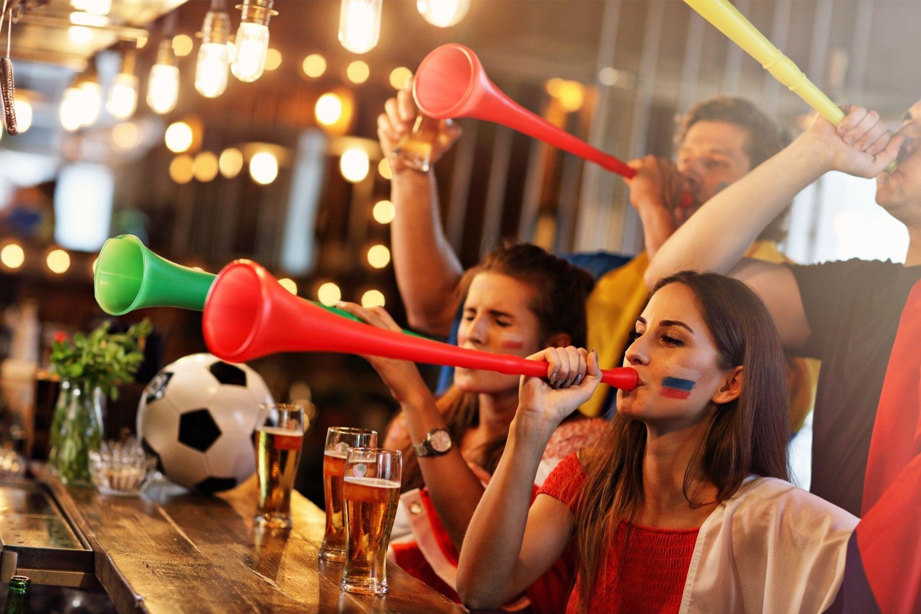 Jóvenes bebiendo y viendo un partido de fútbol en un Sports Bar de Barcelona